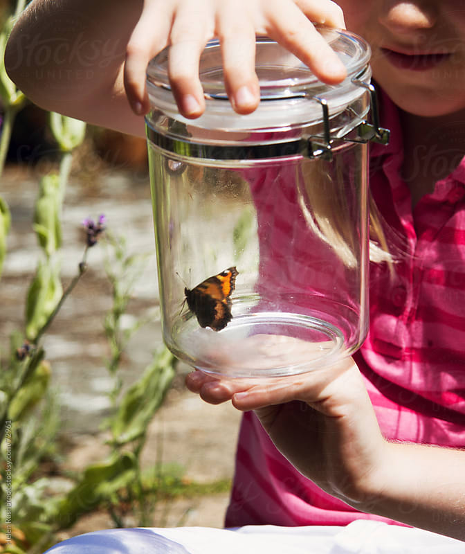 A little girl with a butterfly in a jar by Helen Rushbrook for Stocksy United