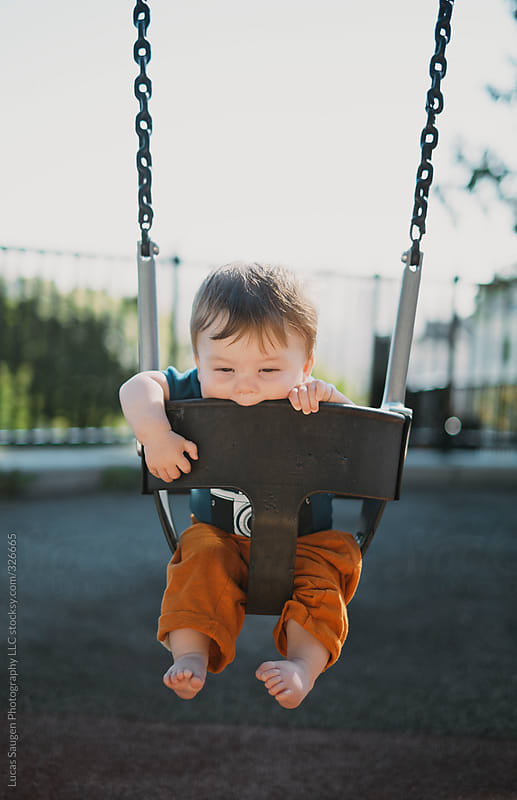 Cute little baby boy swinging on a baby swing. by Lucas Saugen for Stocksy United