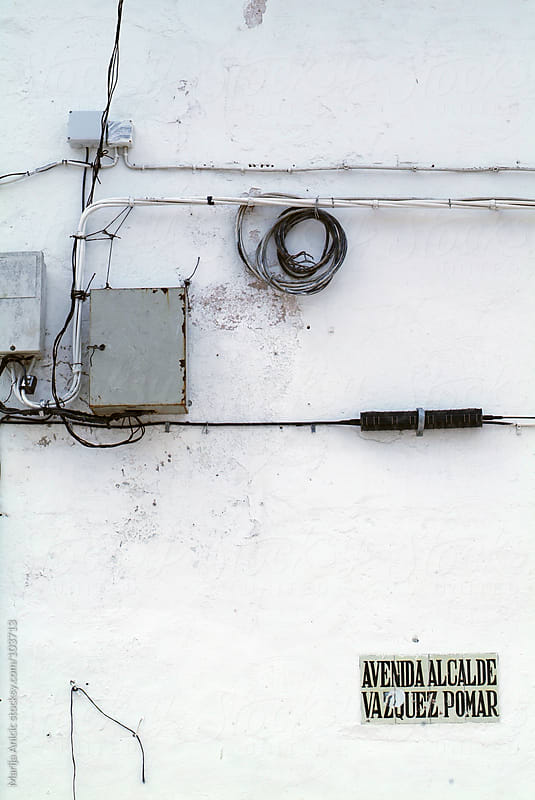 white facade with black wires,electricity box and street name by Marija Anicic for Stocksy United