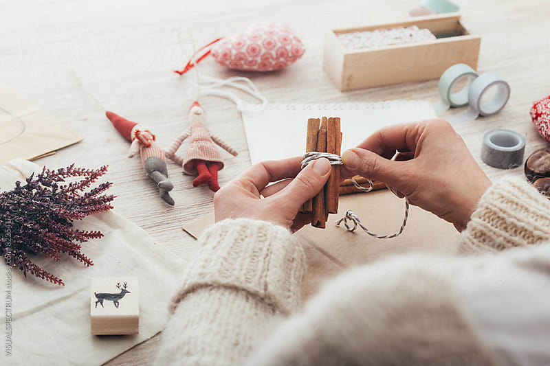 DIY Christmas - Woman Tying Cinnamon Sticks Together for Self-Made Xmas Gift by Julien L. Balmer for Stocksy United