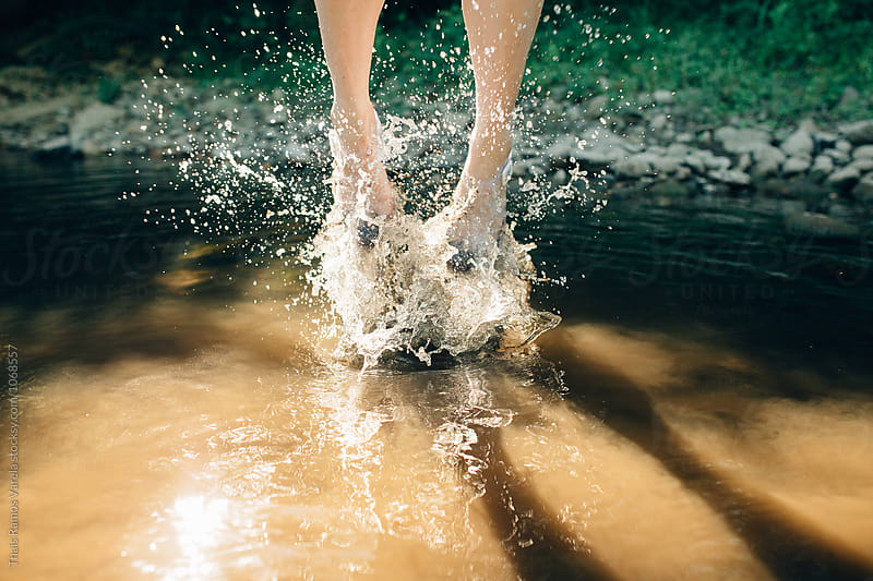 woman jumping in the river by Thais Ramos Varela for Stocksy United