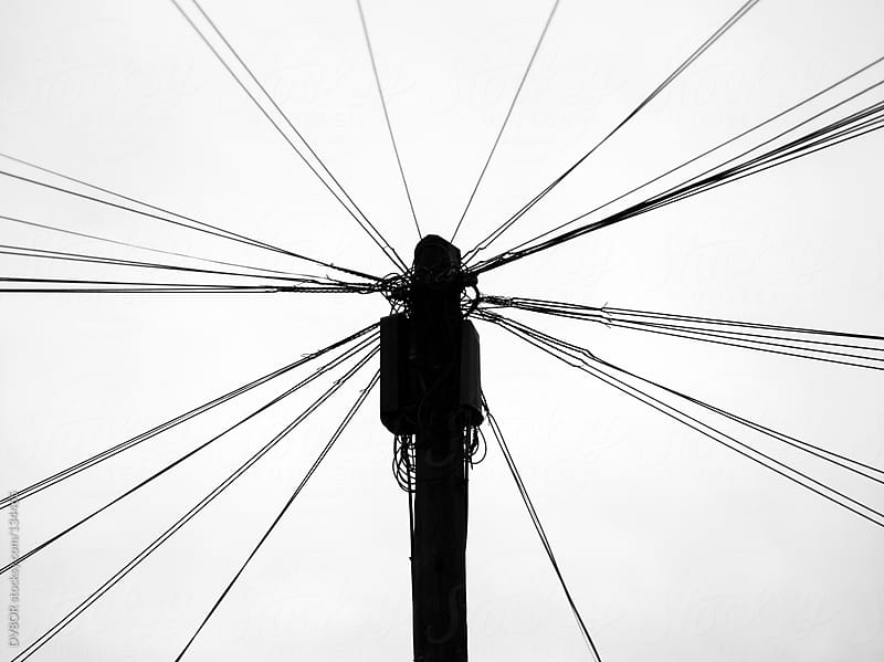 Telephone lines attached to a wooden pole in silhouette by DV8OR for Stocksy United
