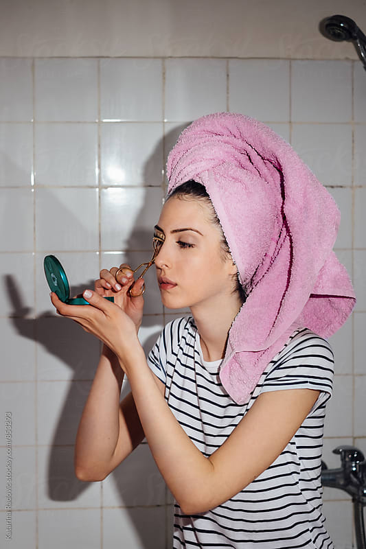 Pretty Young Woman Doing Her Make Up in a Bathroom by Katarina Radovic for Stocksy United