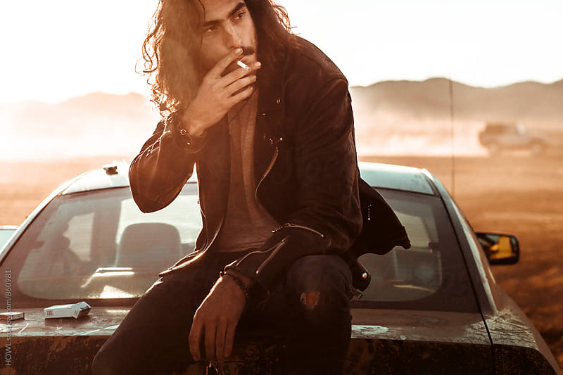 Young hip man smokes a cigarette in the desert  by HOWL for Stocksy United
