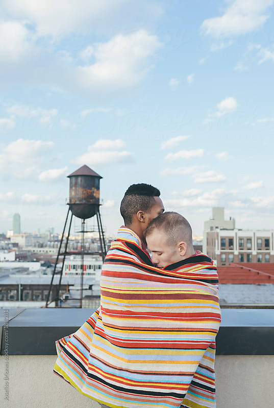 Portrait of Loving Interracial Gay Male Couple Embracing on a Brooklyn Rooftop by Joselito Briones for Stocksy United
