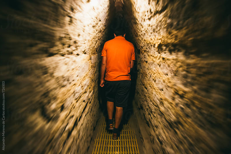 Motion shot of a man walking through an underground tunnel by Alejandro Moreno de Carlos for Stocksy United
