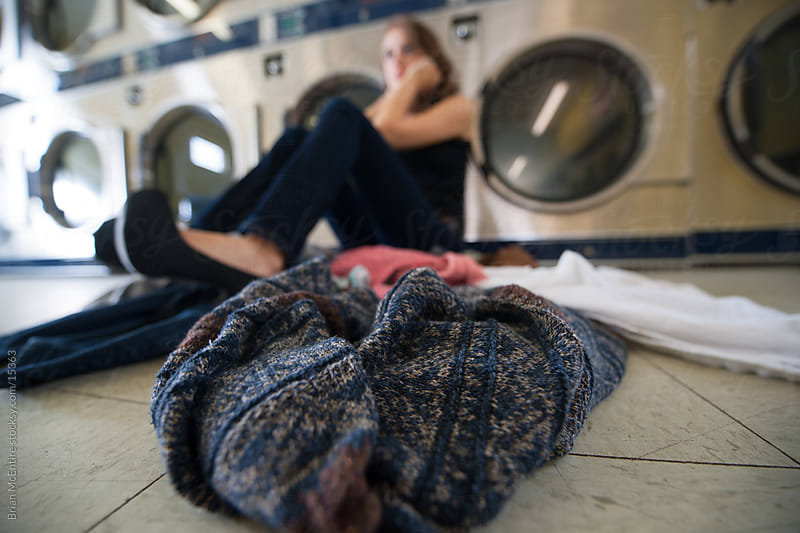 Laundromat: Lonely and Bored Woman Doing Laundry by Brian McEntire for Stocksy United