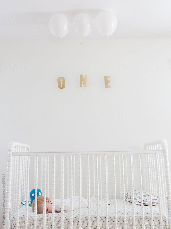 baby asleep in her crib on her first birthday with balloons and the word one by Meaghan Curry for Stocksy United