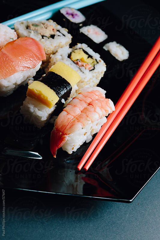 Sushi and chopsticks on black by Paul Phillips for Stocksy United