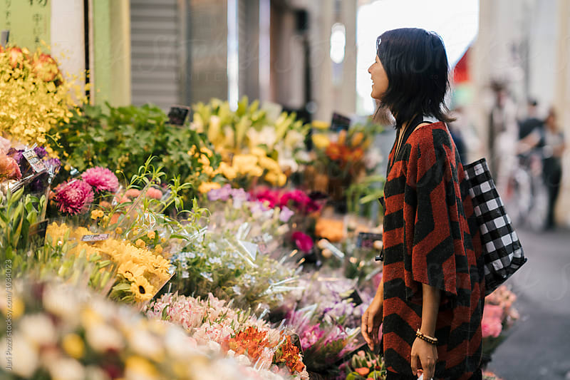 Young asian woman buying Flowers  by Juri Pozzi for Stocksy United