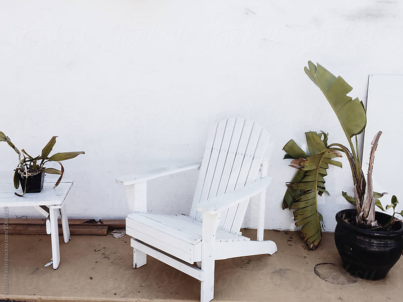 white chair outside white wall with plants by Nicole Mason for Stocksy United