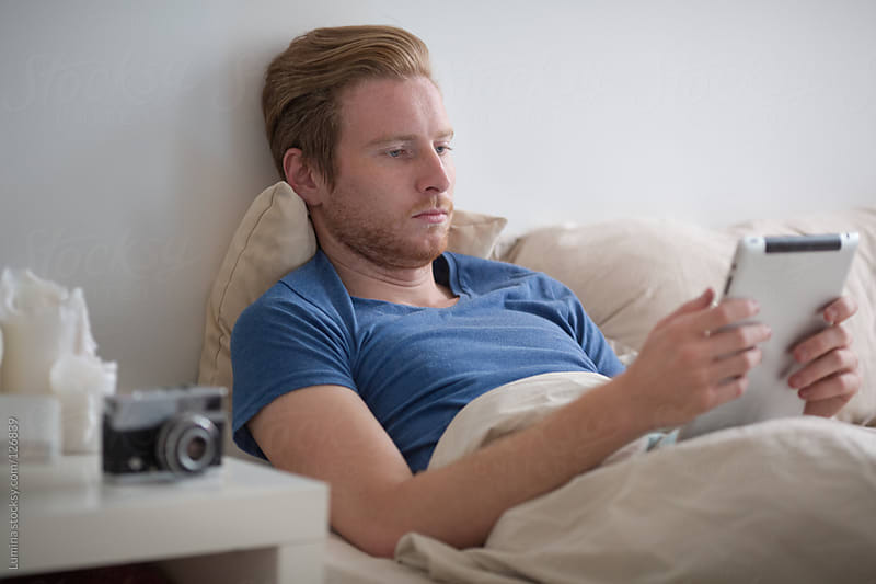 Man Using Tablet in Bed by Lumina for Stocksy United