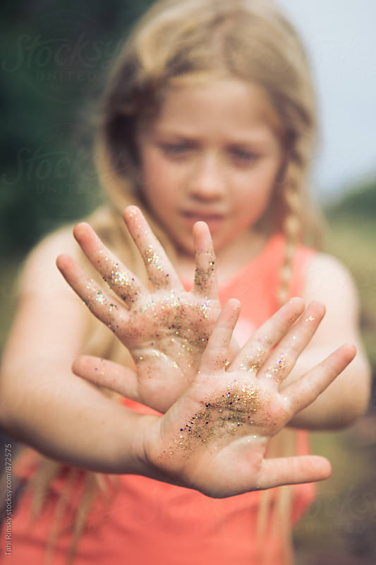 girl showing hands covered in gold glitter  by Tahl Rinsky for Stocksy United