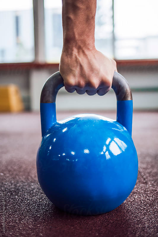 Hand of Man Lifting a Kettle Bell by Lumina for Stocksy United