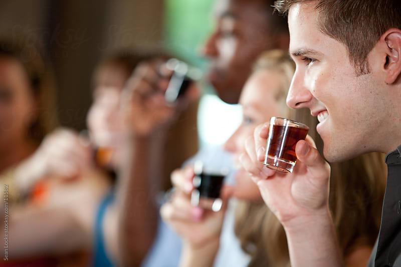 Bar: Friends All Together Drinking Shots by Sean Locke for Stocksy United