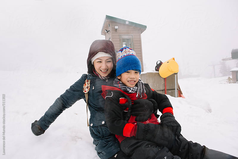 Asian Mommy having fun with her son in the snow by Lawrence del Mundo for Stocksy United