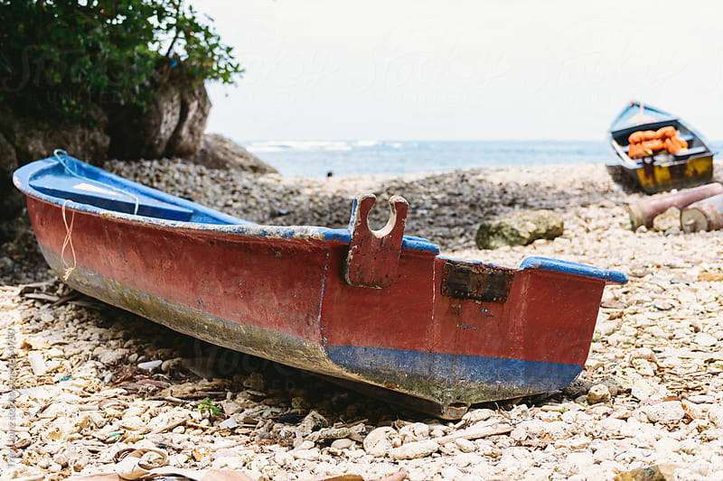 Red and blue fishing boats on rocky shore by Trent Lanz for Stocksy United