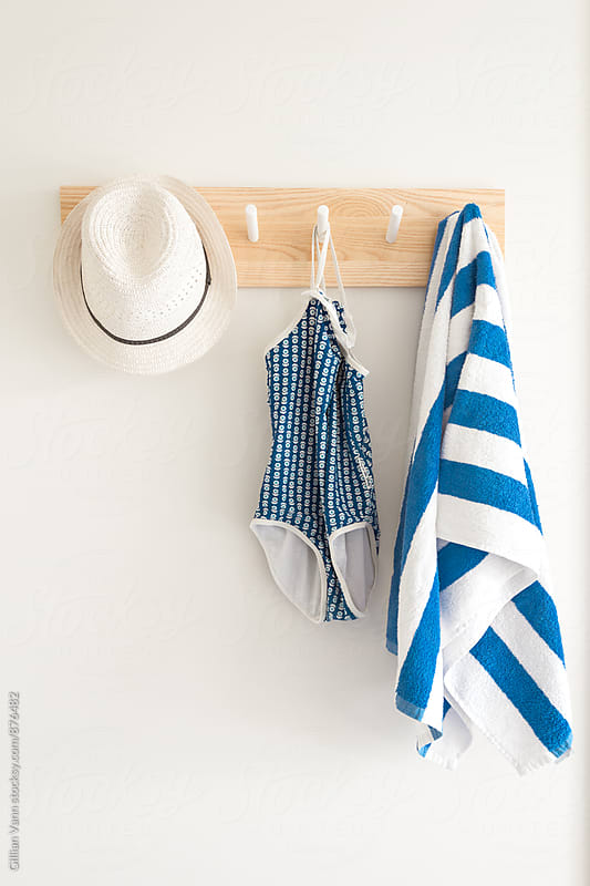 swimsuit and hat hanging on a coat rack by Gillian Vann for Stocksy United