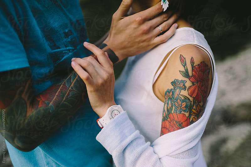 Soft touches of young  tattoo couple by Evgenij Yulkin for Stocksy United