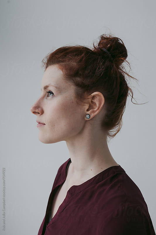 Serious profile portrait of red head woman on simple white background by Rob and Julia Campbell for Stocksy United