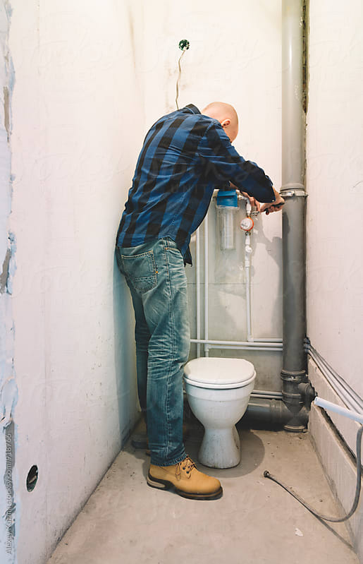 Plumber installing plastic pipes  by Alexey Kuzma for Stocksy United