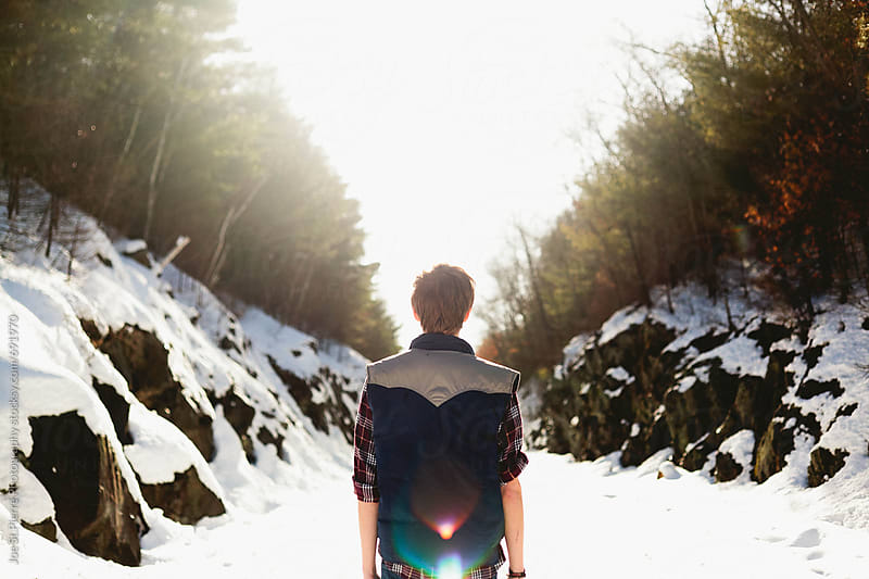 Young man looking down a path by Joe St.Pierre Photography for Stocksy United