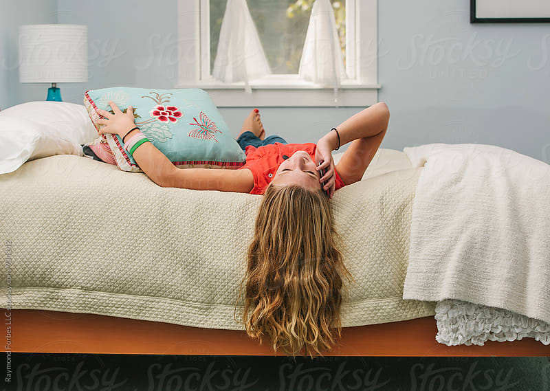 Teen Girl on Cell Phone in Her Bedroom by Raymond Forbes LLC for Stocksy United