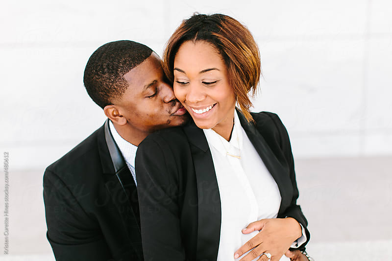 Kissing African American husband and wife by Kristen Curette Hines for Stocksy United