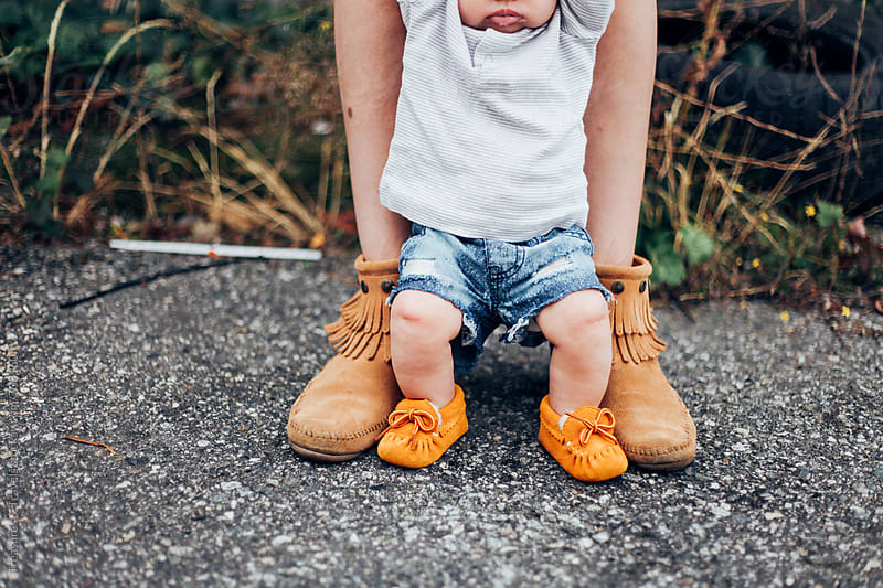 Baby and Mothers feet outdoors by Treasures & Travels for Stocksy United