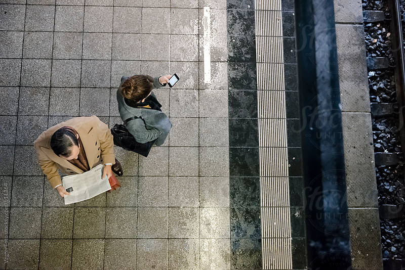Two Business People Waiting For Their Train by VegterFoto for Stocksy United