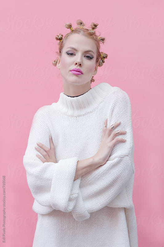 Portrait of a beautiful female model in front of the pink wall by Evil Pixels Photography for Stocksy United