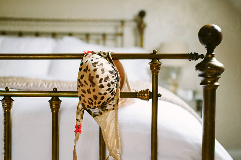 Leopard print lingerie draped over a brass bedstead. by Helen Rushbrook for Stocksy United