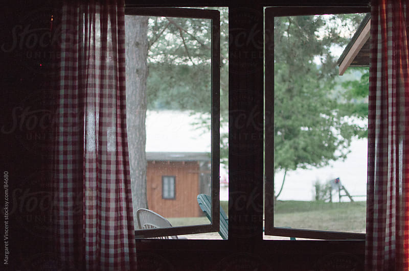 looking through cabin windows  by Margaret Vincent for Stocksy United