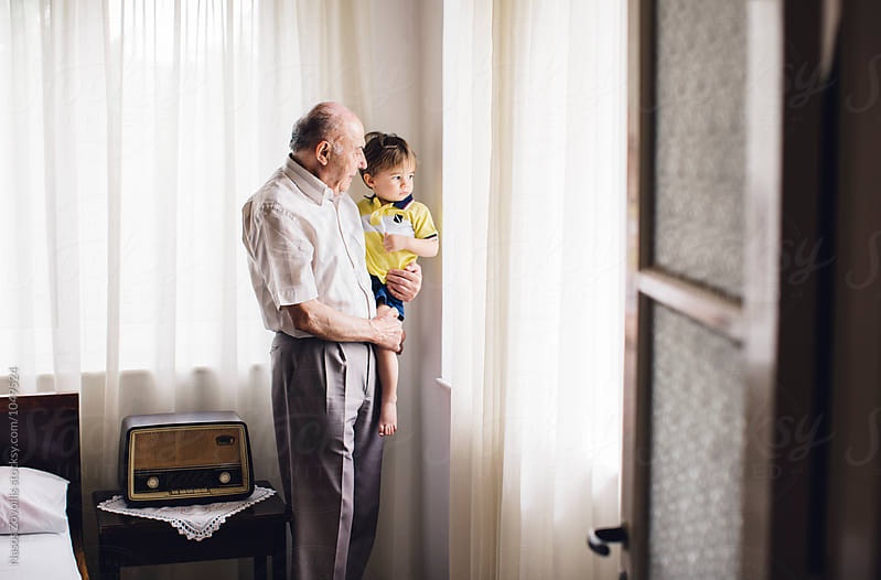 Grandfather with his grandson looking outside of a window by Nasos Zovoilis for Stocksy United
