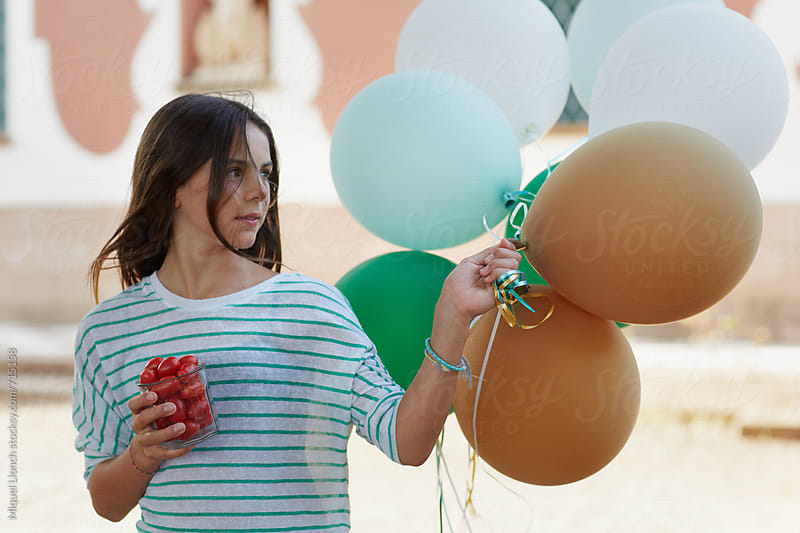 Portrait of a young girl with balloons and tomatoes by Miquel Llonch for Stocksy United