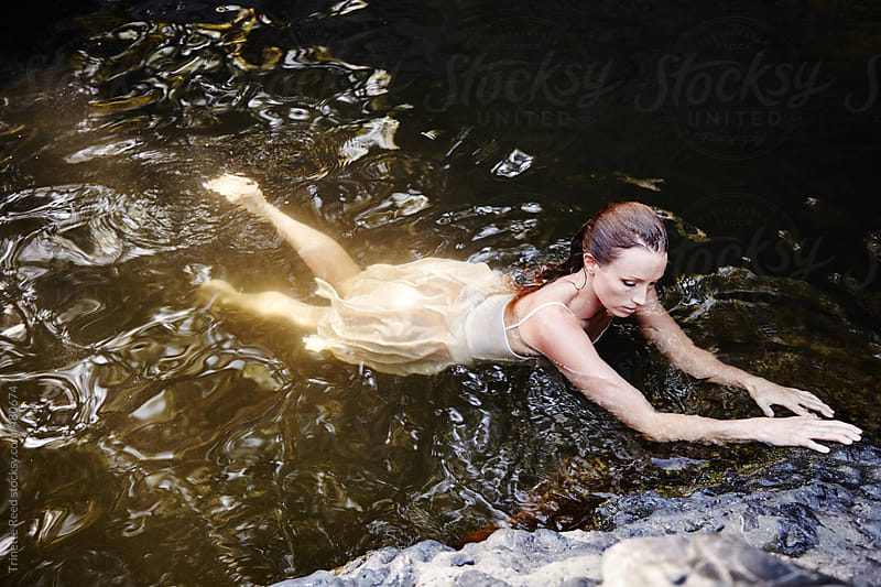 Beautiful redhead woman floating in water  by Trinette Reed for Stocksy United