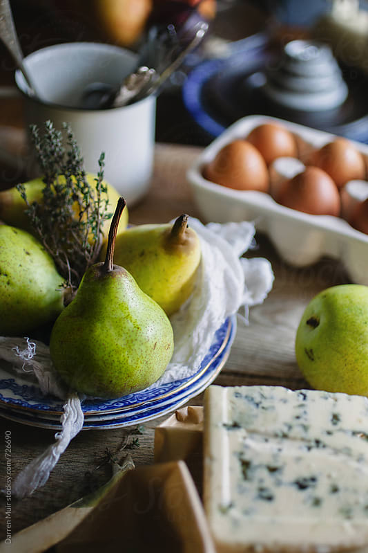Pears,blue cheese and other ingredients ready to be prepped for a dish. by Darren Muir for Stocksy United