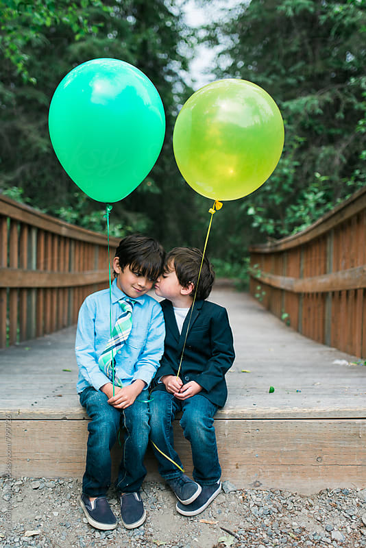 brothers sharing a moment, with balloons by Tara Romasanta for Stocksy United