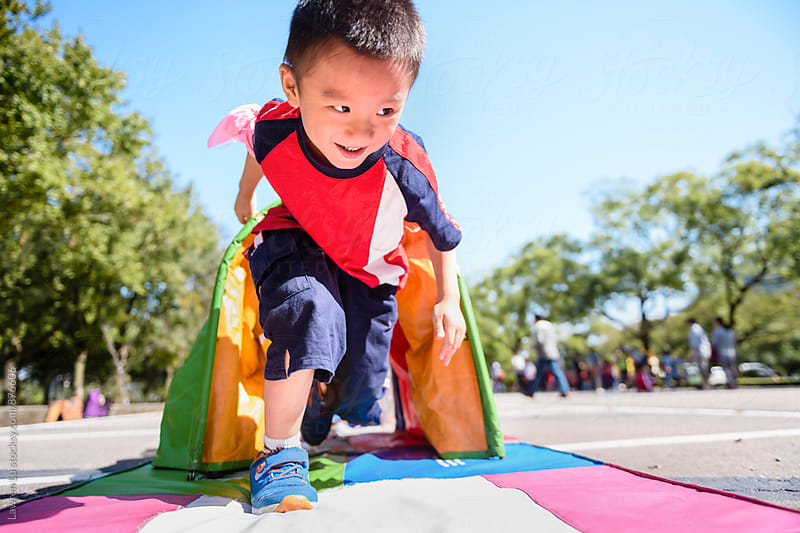 Child runnning out from tent tube on parking lot in sunlight by Lawren Lu for Stocksy United