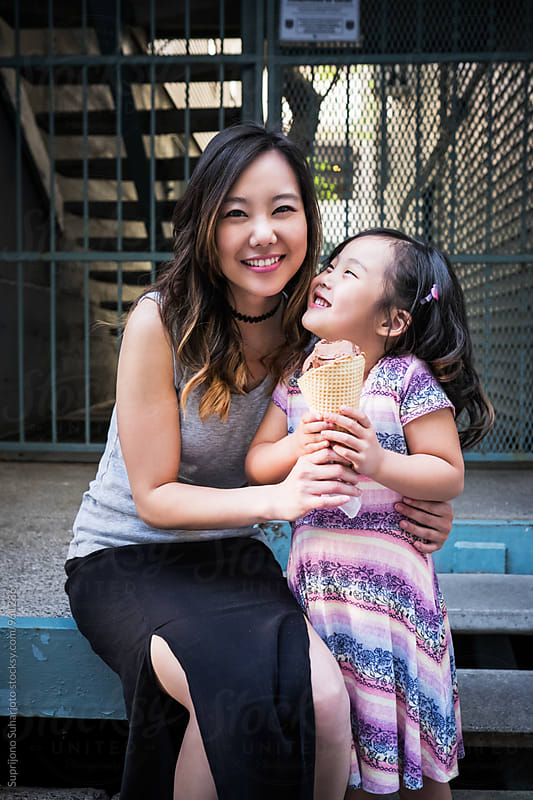 Happy Asian mother and daughter eating ice cream by Suprijono Suharjoto for Stocksy United