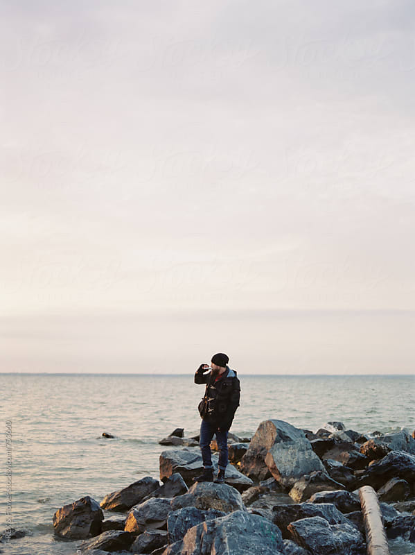 Man drinking from hip flask while standing on rocky shore. by Danil Nevsky for Stocksy United