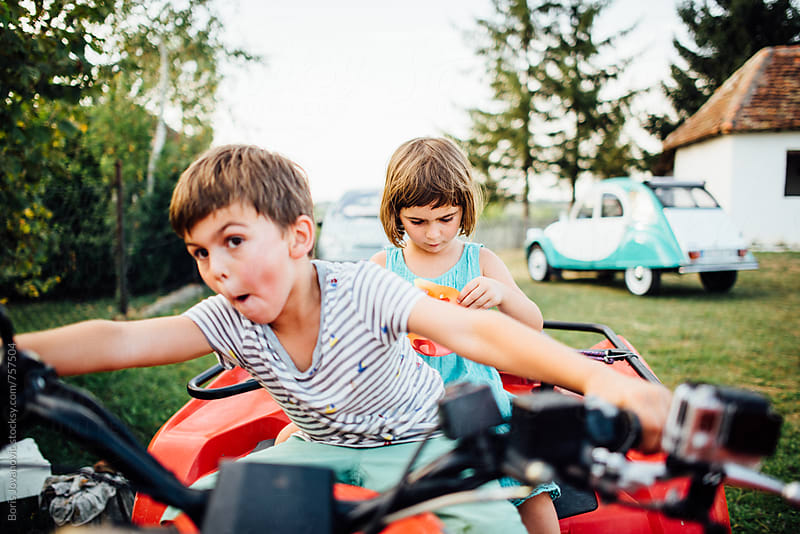Brother and sister having fun on the quad motorbike by Boris Jovanovic for Stocksy United