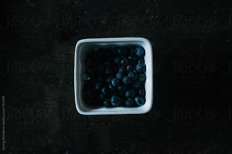 Dark and moody shot of blueberries in porcelain container on dark wood table by Daring Wanderer for Stocksy United