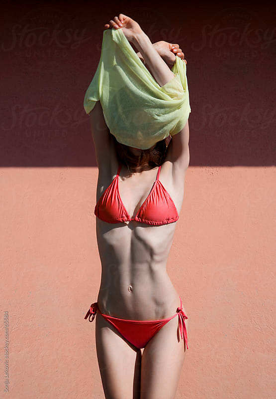 attractive woman in a red swimsuit undressing in the sun by Sonja Lekovic for Stocksy United