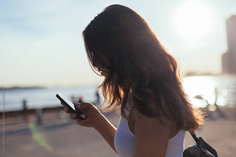 Brunette checking the phone in New York City by Good Vibrations Images for Stocksy United