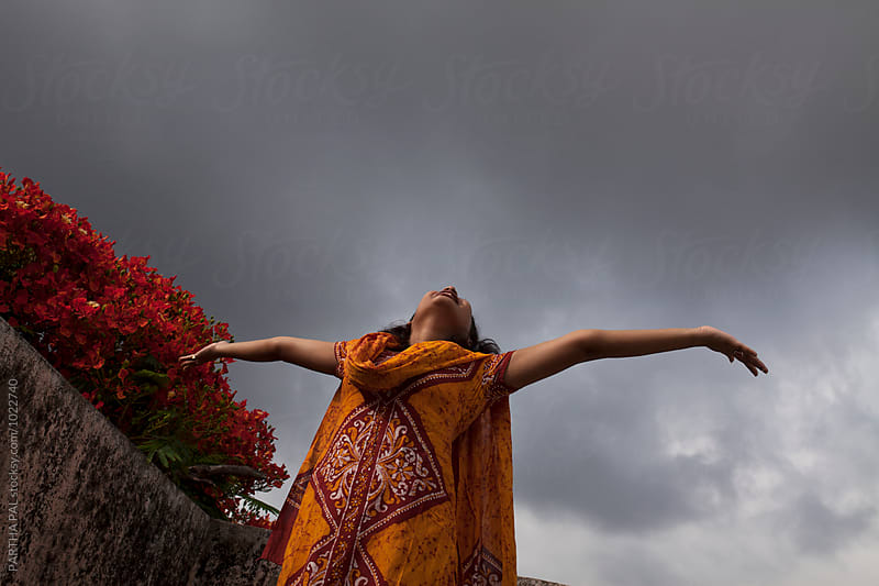 A young woman stretched arm with monsoon sky backdrop by PARTHA PAL for Stocksy United