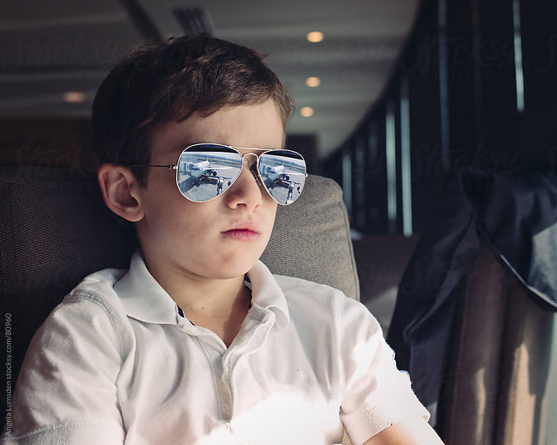 Boy with reflective sunglasses at an airport by Angela Lumsden for Stocksy United