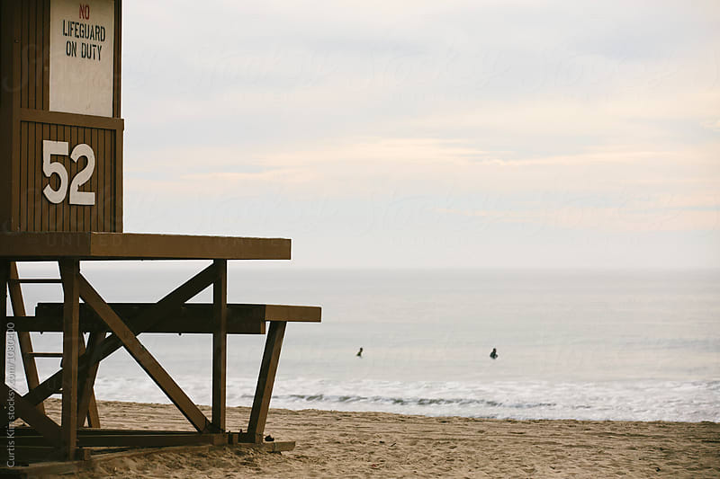 Lifeguard tower with ocean and surfers in the water by Curtis Kim for Stocksy United