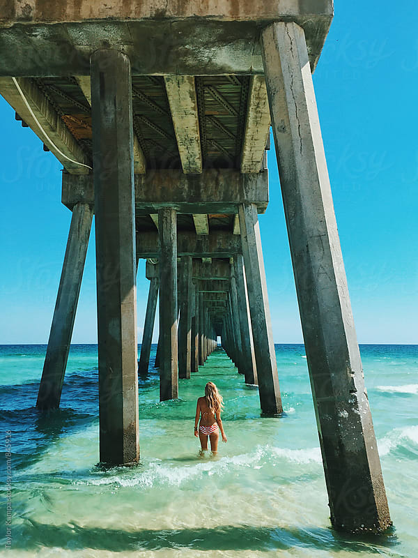 Girl Under a Pier by Taylor Kampa for Stocksy United