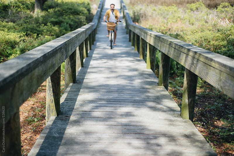 Man on a bicycle rides up a wooden boardwalk by Cara Dolan for Stocksy United